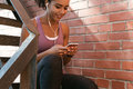 Young woman sitting outdoors, texting message