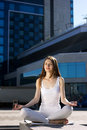 Young woman sitting outdoors in yoga pose on urban background Stock Images