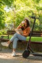 A young woman is sitting on a park bench, reading book and drinki Royalty Free Stock Photo