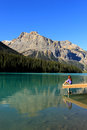 Young woman sitting on a pier at emerald lake yoho national par park british columbia canada Stock Image