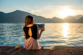 Young woman sitting on the pier at sunrise Royalty Free Stock Photo