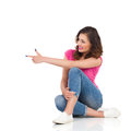 Young woman sitting and pointing cheerful in pink shirt jeans on a floor looking away full length studio shot isolated on Royalty Free Stock Images