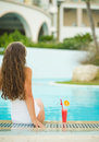 Young woman sitting at poolside with cocktail Royalty Free Stock Photos