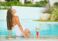 Young woman sitting at poolside with cocktail long hair Stock Photo
