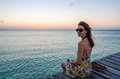 Young woman sitting on seaside jetty at sunset adorable in stylish sun dress and enjoying beautiful in the caribbean sea paradise Royalty Free Stock Photography