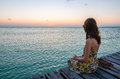Young woman sitting on seaside jetty at sunset adorable in stylish sun dress and enjoying beautiful in the carribean sea paradise Royalty Free Stock Image