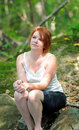 Young woman sitting in shadows - woods Royalty Free Stock Photo