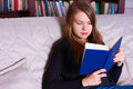 Young woman sitting on sofa at home reading a book portrait of beautiful girl Stock Photos