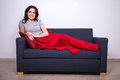 Young woman sitting on sofa wrapped in red blanket happy Stock Image