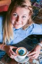 Young woman sitting at a table holding a coffee cup with her face printed on the foam. Royalty Free Stock Photo