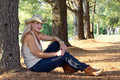 Young woman sitting between trees pretty wearing cowgirl hat outdoors by large Royalty Free Stock Image