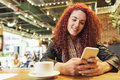 Young woman sitting in trendy cafe writing with her mobile phone Royalty Free Stock Photo