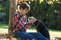 Young woman sitting under an autumn tree cuddling her black dog outside in a park Royalty Free Stock Photography