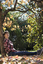 Young woman sitting under autumn tree leaning on its trunk enjoying a beautiful sunny day in a park Stock Photo
