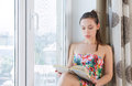 Young woman sitting in a windowsill beautiful with book Stock Photography