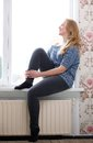 Young woman sitting on windowsill portrait of a and looking out window Stock Photos