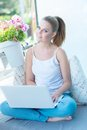 Young woman sitting working on a laptop computer beautiful casual an outdoor porch hot sunny day Stock Images