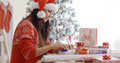 Young woman sitting wrapping Christmas gifts Royalty Free Stock Photo