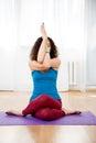 Young woman sitting in yoga pose mix gomukhasana and garudasana Royalty Free Stock Photo