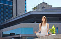 Young woman sitting in yoga pose outdoors near green flower on modern building background Stock Images