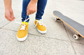 Young woman skateboarder tying shoelace at modern city Stock Images