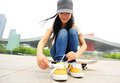 Young woman skateboarder tying shoelace at modern city Stock Photo