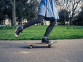 Young woman skateboarding in the park a wearing trendy clothes is a Stock Photo