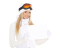 Young  woman in ski glasses with empty board for the text. Royalty Free Stock Photo
