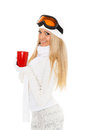 Young woman in ski glasses with red cup and winter warm clothes stands on a white background winter sports Royalty Free Stock Photos