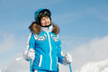 Young woman in ski suit stands and looks Stock Photo