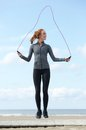Young woman skipping with jump rope outdoors Royalty Free Stock Photo