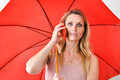 Young woman smart phone umbrella an attractive with a red and an Royalty Free Stock Photo
