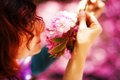 Young woman smelling a beautiful sakura blossom, purple flowers. Spring Magic Royalty Free Stock Photo