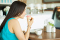 Young woman smelling a cupcake profile view of pretty brunette while having some coffee in cake shop Stock Photos