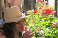 Young woman smelling at flowers wearing a hat Royalty Free Stock Image