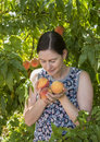Young Woman Smelling Fresh Peaches. Royalty Free Stock Photo