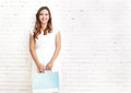 Young woman smiling while carrying shopping bags portrait of with white brick wall on the background with copyspace Royalty Free Stock Photos