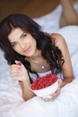 Young woman smiling eating fruit salad raspberry beautiful happy with perfect teeth healthy of strawberries raspberries Stock Photography