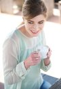 Young woman smiling and enjoying a cup of coffee portrait Royalty Free Stock Image