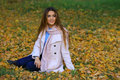 Young woman smiling sitting on the grass in the autum. fall yellow maple garden background Royalty Free Stock Photo
