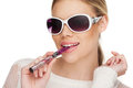 Young woman smokin electic cigarette e wearing sunglasses Royalty Free Stock Images