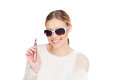 Young woman smokin electic cigarette e wearing sunglasses Royalty Free Stock Photo