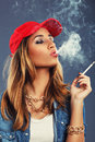Young woman smoking cigarette on a blue background Stock Photography