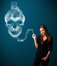 Young woman smoking dangerous cigarette pretty with toxic skull smoke Stock Photo