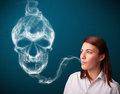 Young woman smoking dangerous cigarette pretty with toxic skull smoke Stock Image