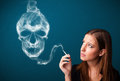Young woman smoking dangerous cigarette with toxic skull smoke Stock Photography