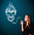 Young woman smoking dangerous cigarette with toxic skull smoke pretty Stock Photo