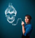 Young woman smoking dangerous cigarette with toxic skull smoke pretty Royalty Free Stock Image