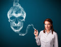 Young woman smoking dangerous cigarette with toxic skull smoke pretty Royalty Free Stock Photography