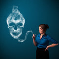 Young woman smoking dangerous cigarette with toxic skull smoke Royalty Free Stock Photo